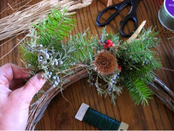 Small bouquets of material are added to build the wreath, and each is secured to the base by wrapping the stem ends with metal wire.