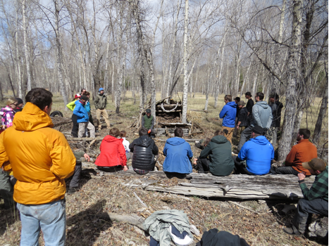 This photo shows an Aerie instructor discussing the finer points of shelter construction with students.