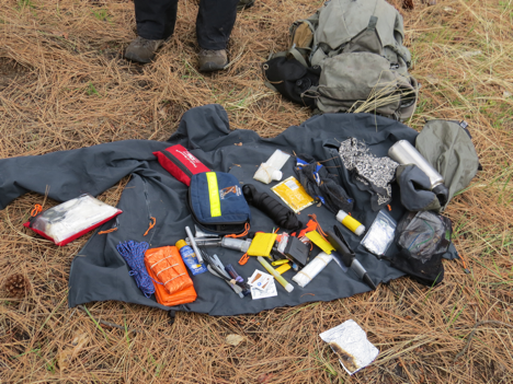 This photo shows a survival kit that an instructor has pulled apart to show the contents to students.